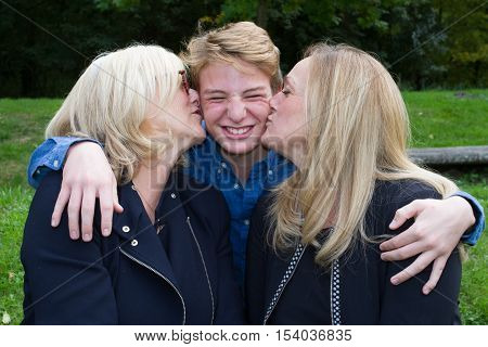 Grand Mother And Daughter Kissing Son Outside