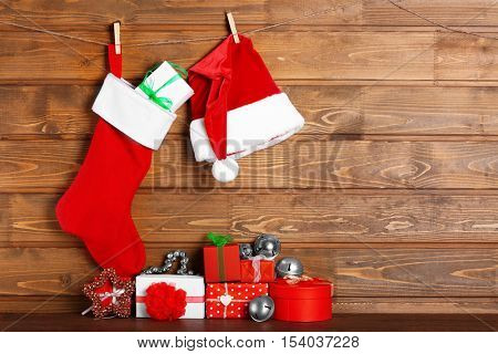 Christmas stocking, Santa Claus hat and presents against wooden background