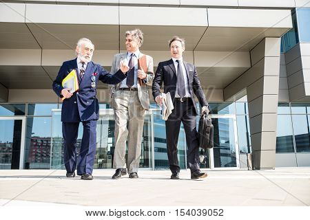 Three senior businessmen walking outdoors - Managers talking about business