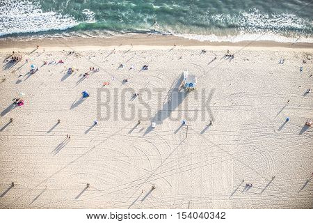 Santa Monica beach drone view - People sunbathing on the beach and swimming in the ocean