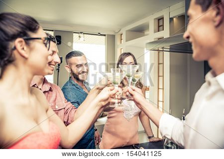 Group of friends having party at home and toasting cocktail glasses