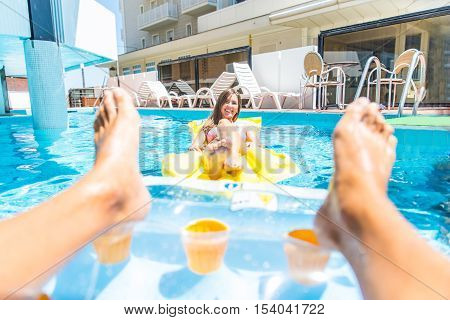 Couple of friends relaxing on air mattress in a swimming pool - Summer holidays lovers sunbathing in a pool