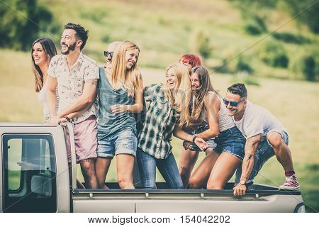 Group of friends driving on the back of pick-up car and having fun - People on vacation and enjoying an excursion in the nature