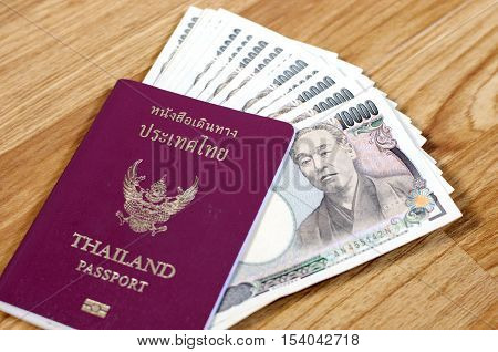 Thailand passport with Japanese banknotes - Stock Photo