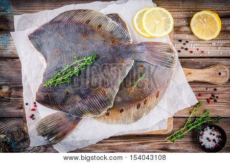 Raw flounder fish flatfish on wooden background