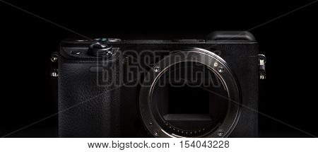 mirrorless camera body on dark black background