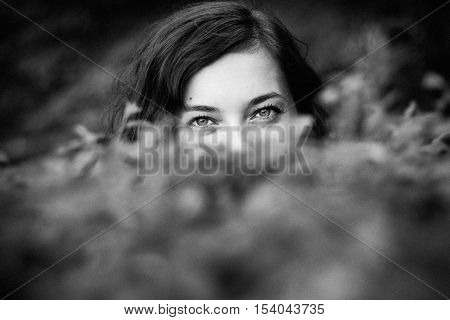 Monochrome glance from a woman behind the bushes.