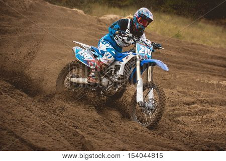 24 september 2016 - Volgsk, Russia, MX moto cross racing - Girl Bike Rider rides on a motorcycle and throwing a spray of dirt, telephoto