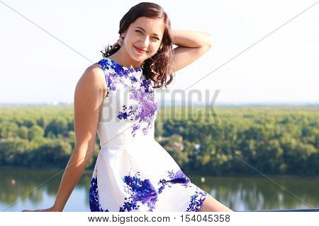 Beautiful young girl sits and looks at the camera, the girl sitting on the railing of the city