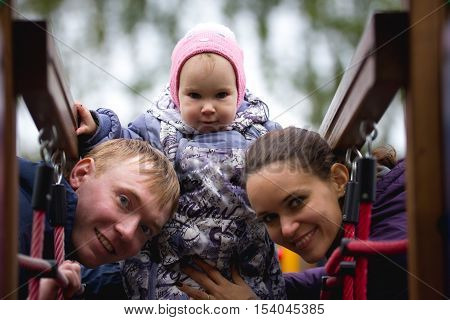 Happy family: Father, Mother and child - little girl walking in autumn park: mamy, dad and baby playing at playground, close up, telephoto shot