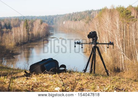 Camera standing on tripod at morning on forest river landscape, spring in Ural, wide angle