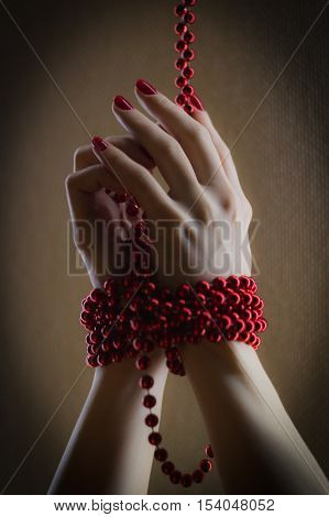 Girl has hands bound with red beads - illustrate pretty nail manicure, extremely close up