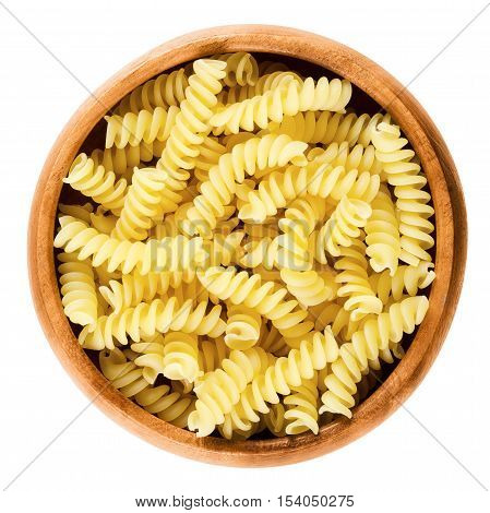Girandole torsades pasta in wooden bowl. Uncooked dried durum wheat semolina pasta. Single S-shaped strand of noodles twisted in a loose spirals. Isolated macro food photo over white background.
