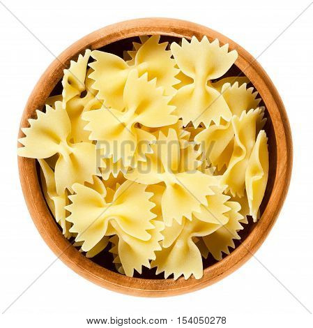 Farfalle pasta in wooden bowl. Uncooked dried durum wheat semolina pasta. Decorative short-cut bow tie or butterfly shaped Italian noodles. Isolated macro food photo over white background.