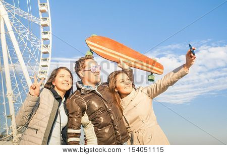 Young hipster people trio taking selfie at luna park ferris wheel - Friendship and wanderlust concept with best friends having fun together at trip travel around the world - Warm afternoon color tones