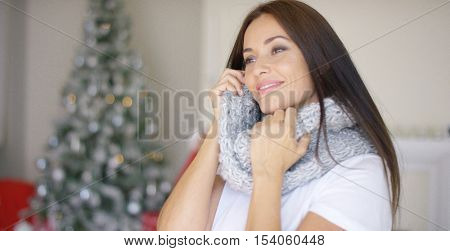Dreamy young woman snuggling into her scarf