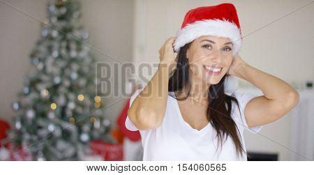 Pretty vivacious woman donning a Santa hat
