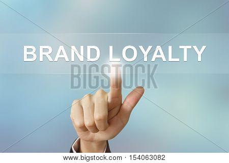 business hand pushing brand loyalty button on blurred background