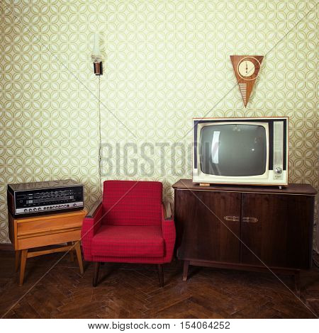 Vintage room with wallpaper, tv, old fashioned armchair, retro player, loudspeakers, clocks and standart lamp, toned