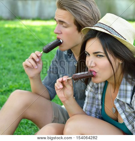 Young man and women eating chocolate ice-cream outdoor in summer park. Friends have fun outdoor. Leisure, youth, summertime. Young couple eat ice-cream together.