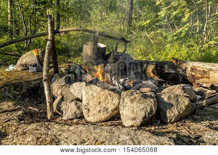 A pot of food hanging over an open fire outdoors on a picnic in the summer