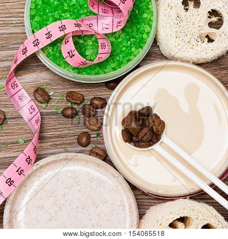 Anti-cellulite cosmetic products with caffeine. Close-up of open jars filled with cellulite cream containing coffee essential oil, sea salt, natural body scrub, coffee beans and body measuring tape