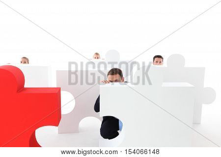 Business people hiding behind puzzle pices on white