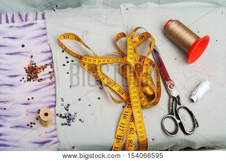 Sewing textile or cloth. Work table of a tailor. Textile tools. Scissors reel of thread, measuring tapes and natural fabric. Copy space. Top view.