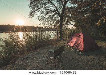 Camping With Tent, Chairs And Camping Gear. Sunrise Over Okavango River, Namibia Botswana Border. Ad