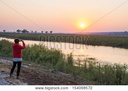 Tourist taking photo with smartphone at majestic sunset over Chobe River Namibia Botswana border Africa. Natural colors rear view.