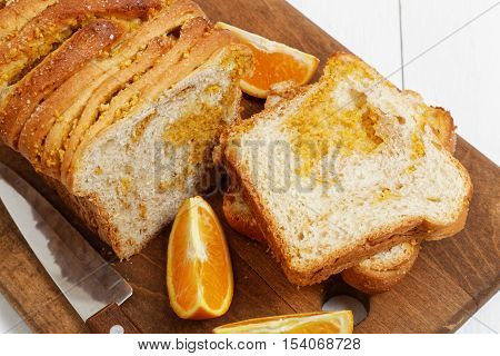 Closeup homemade bread with orange zest and walnuts on white wooden table. Near a knife and slices of fresh oranges.