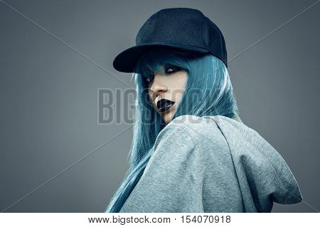 Young womanwith cyan color hair in hoodie and cap