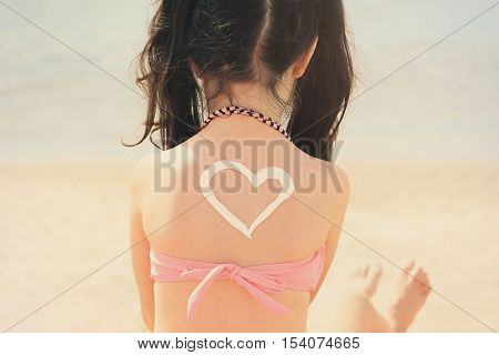Little girl with sunscreen in heart shape on back. Skin care concept.
