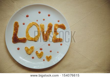 Breakfast with love. Pancakes with red currant jam for breakfast. The word love and hearts made ​​out of pancakes lie on a white plate on a wooden table