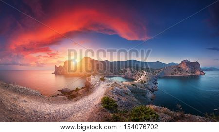 Amazing summer landscape with mountains sea blue sky sun and beautiful colorful red clouds at sunset in Crimea. Sunset in mountains. Panoramic. Nature background. Vibrant landscape in twilight.