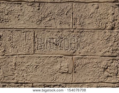 Brown stucco is shaped to resemble cinder blocks, forming an irregular pattern that can be used for backgrounds.