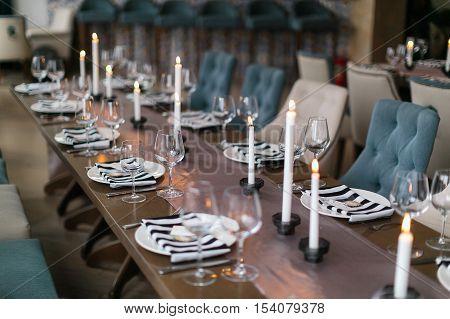 Wedding decor. Wedding interior. Festive decor. Table decor. Table layout. Pastel tone. Restaurant interior. The burning candles on a table.