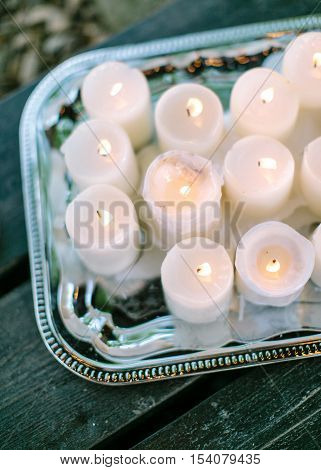Wedding decor. Wedding interior. Romantic decor. The burning candles on a vintage tray. Candles close up. The vague image. The image in a rasfokus. Silhouette of candles.