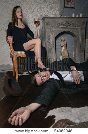 A scene from the film. Femme Fatale committed murder. The body of a man lying on the floor. Woman holding a glass of whiskey. Woman is sitting in armchair put her leg on guy