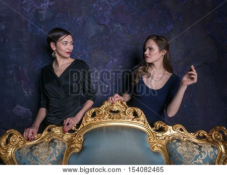 Two girls look at each other. Haughty eyes. A scene from the film. Girls from high society. Shooting in studio. Stage image. Interior vintage. Glamour vintage style