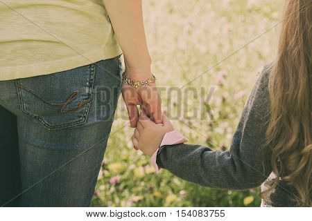 Young mother holding her little daughter by the hand. Summer green meadow with flowers. Summer family trip. Childhood. Reliability. Parent support