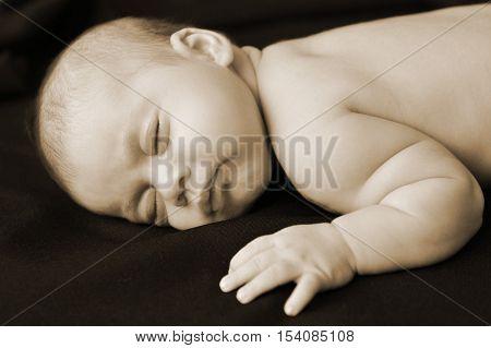 A newborn baby sleeps on a black blanket in peace.