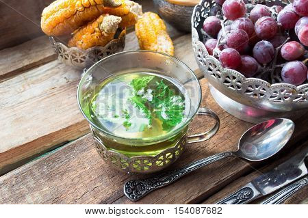 Mint tea in vintage silver cup with grapes on wooden background. Selective focus, close up.