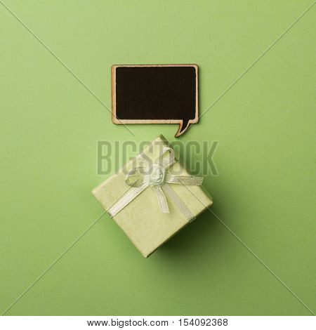top view of small gift box on green background with wooden black chalk board speech bubble for text