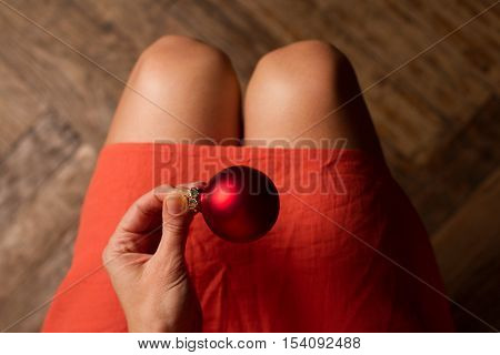 Top view of woman with red dress holding one red Christmas globe above her knees