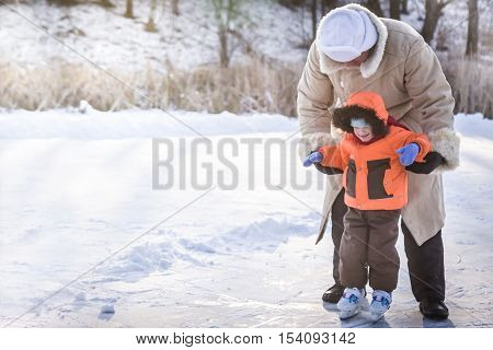 Family enjoying ice skating on outdoors skating rink in a snowy park during winter holidays