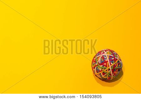 Close up of an elastic ball on a yellow background.