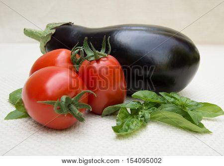 Three Roma Tomatoes, Fresh Basil and an Eggplant Photographed at Eye Level