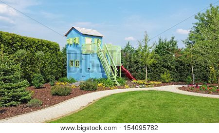 Wooden two floors play house for kids in corner of the garden. Summer time, good sunny weather.