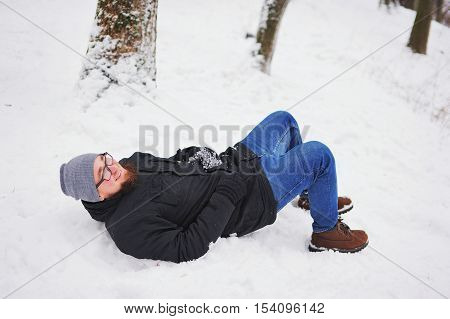 A young bearded man lying in the snow and laughing merrily in the Park.